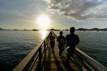 Keindahan Labuan Bajo Nusa Tenggara Timur bisa dinikmati dengan berbagai cara. Salah satunya dengan menikmati matahari terbenam di dermaga kayu sambil berenang.